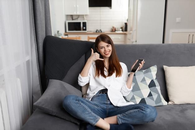 Enthousiaste femme parlant au téléphone assis sur le canapé au repos dans l'appartement.