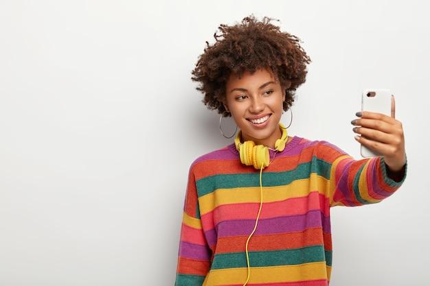 Enthousiaste femme à la peau sombre avec des cheveux bouclés sombres, fait selfie via smartphone, vêtue d'un pull coloré, sourit doucement, se dresse sur fond blanc, espace vide de côté