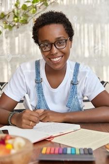 Enthousiaste femme à la peau sombre avec coupe de cheveux afro, apprend le matériel pour l'examen universitaire