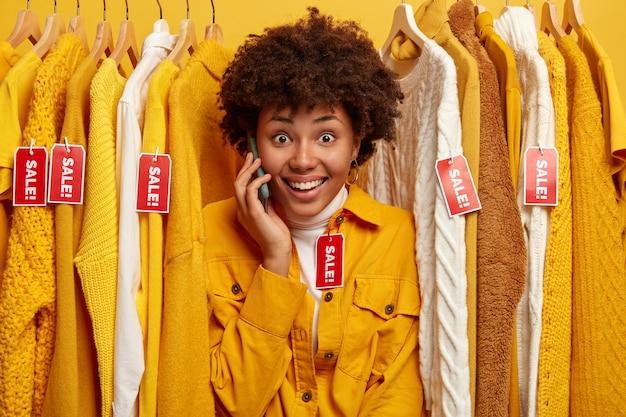 Enthousiaste femme à la peau sombre avec un sourire charmant, se tient entre les vêtements avec des étiquettes rouges inscrites vente, regarde avec plaisir la caméra