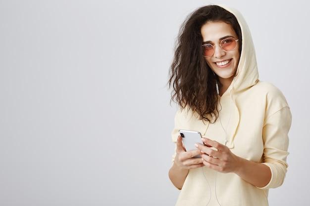 Enthousiaste femme souriante à l'aide de téléphone mobile