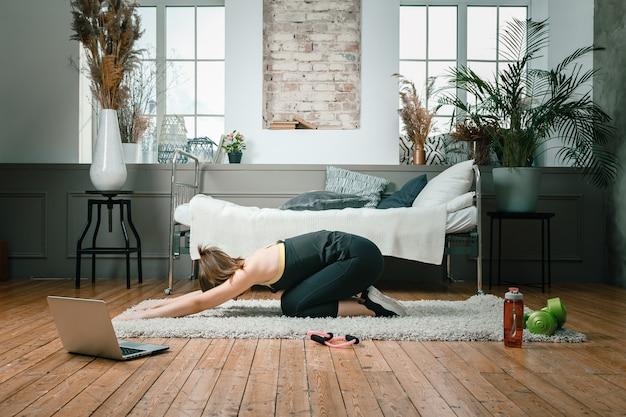 Enthousiaste femme sportive aux cheveux rouges s'étire jusqu'à la jambe dans la chambre