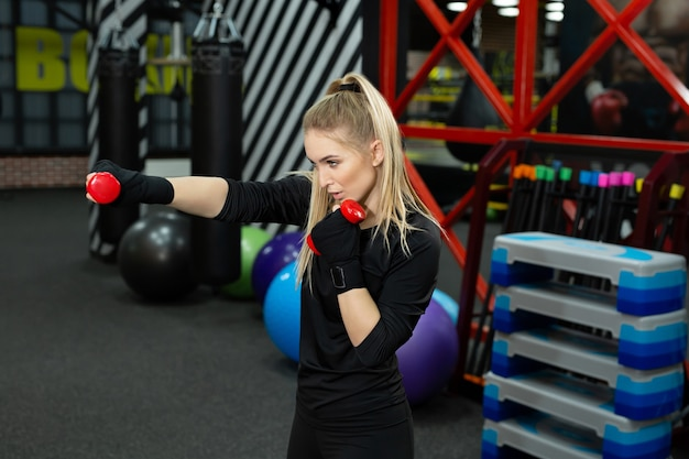 Enthousiaste femme sportive exerçant un coup de poing à la main avec des haltères en ring de boxe