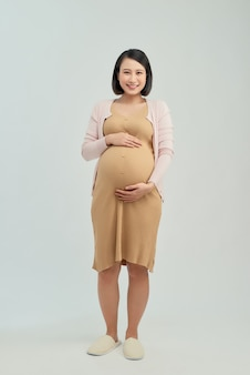 Enthousiaste fille asiatique enceinte touchant le ventre sur blanc