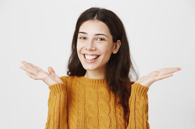 Enthousiaste fille brune souriante écarter les mains sur le côté, terminer les examens facilement, ne vous inquiétez pas