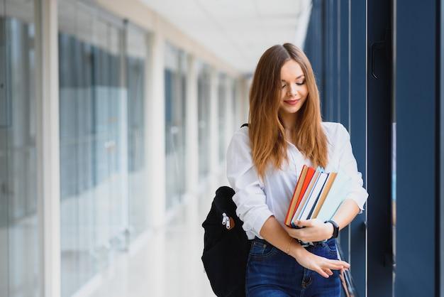 Enthousiaste fille étudiante brune avec sac à dos noir détient des livres dans un bâtiment moderne