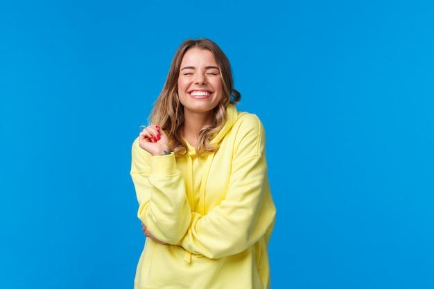 Enthousiaste fille heureuse insouciante se sentir heureuse et ravie, fermer les yeux rêveur souriant avec un sourire rayonnant parfait, toucher une mèche de cheveux, debout dans un sweat à capuche jaune