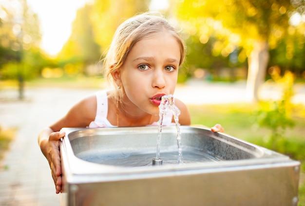 Enthousiaste fille merveilleuse boit de l'eau fraîche à partir d'une petite fontaine dans un parc ensoleillé chaud d'été sur des vacances tant attendues