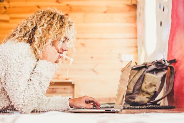 Enthousiaste heureuse belle blonde frisée caucasienne femme travaillant à l'ordinateur portable se coucha sur le sol à la maison ou à l'hôtel pour les vacances de voyage bureau alternatif pour un emploi gratuit et les voyages