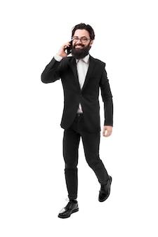 Enthousiaste homme d'affaires en tenue de soirée, parler au téléphone, isolé sur fond blanc