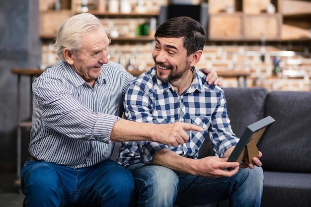 Enthousiaste homme âgé reposant sur le canapé avec son fils et pointant le cadre photo