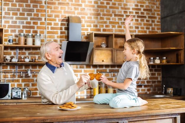 Enthousiaste homme âgé souriant dégustation de pâtisseries faites maison avec sa petite-fille en se tenant debout dans la cuisine