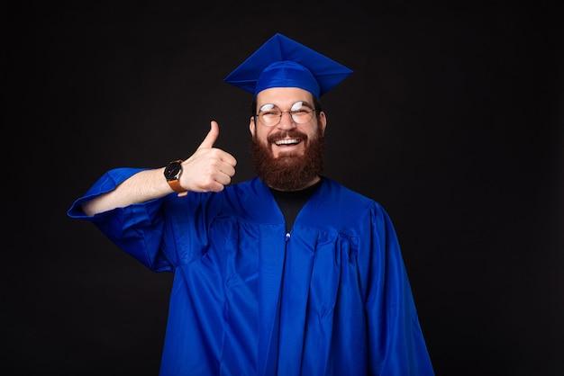 Enthousiaste homme étudiant heureux portant baccalauréat montrant le pouce vers le haut