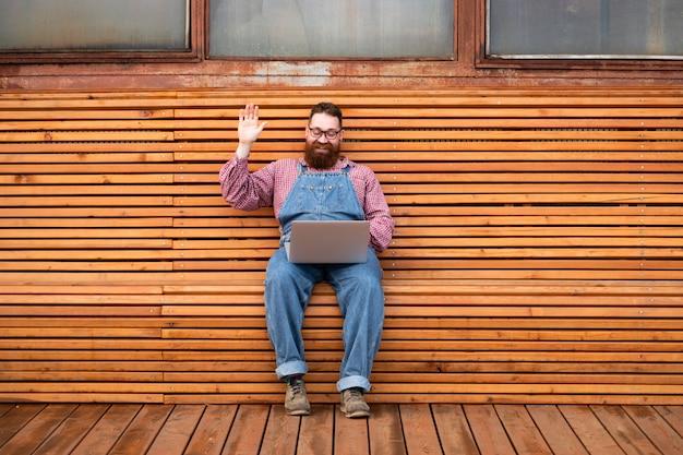 Enthousiaste homme hipster barbu brutal à l'aide d'un ordinateur portable parle avec sa petite amie et en agitant la main, dit bonjour, assis sur un banc à l'extérieur
