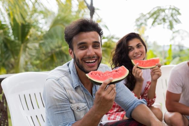 Enthousiaste homme latine avec tranche de pastèque sourire ensemble