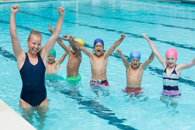 Enthousiaste instructeur féminin avec des enfants profitant de la piscine