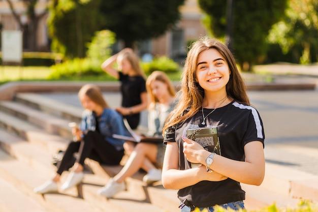 Enthousiaste jeune adolescente avec livre près d'amis