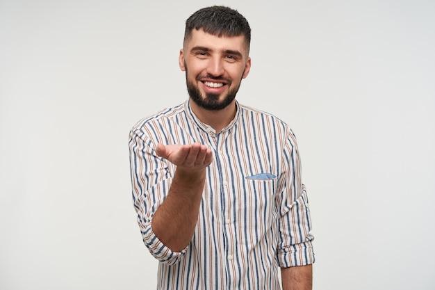 Enthousiaste jeune beau mâle barbu aux cheveux noirs vêtu de vêtements décontractés gardant sa paume levée et à la recherche avec un sourire charmant, isolé sur un mur blanc