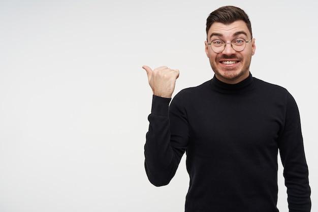 Enthousiaste jeune beau mec brune barbu aux cheveux courts pointant de côté avec la main levée et regardant joyeusement avec un large sourire, posant sur blanc