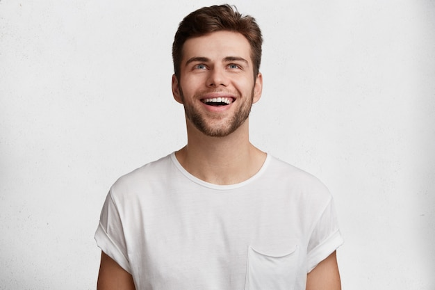 Enthousiaste jeune beau mec en t-shirt décontracté, isolé sur fond de studio blanc, remarque quelque chose d'agréable au plafond, exprime des émotions et des sentiments positifs. concept d'expressions faciales.