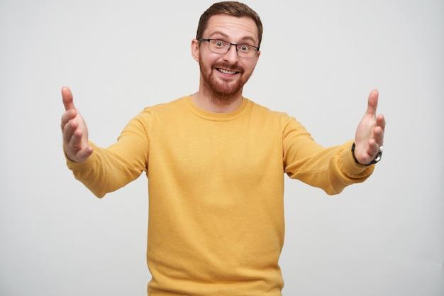 Enthousiaste jeune bel homme brune à lunettes avec barbe posant avec les bras grands ouverts, à la recherche positive et souriant joyeusement