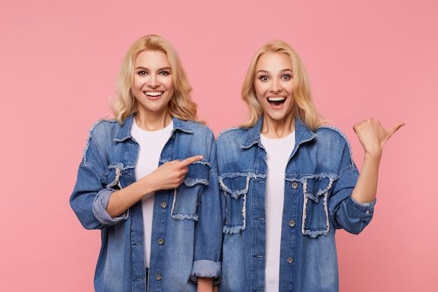 Enthousiaste jeune belle femme aux cheveux longs à tête blanche souriant joyeusement tout en montrant de côté avec la main levée, isolée sur fond rose en manteaux de jeans bleu