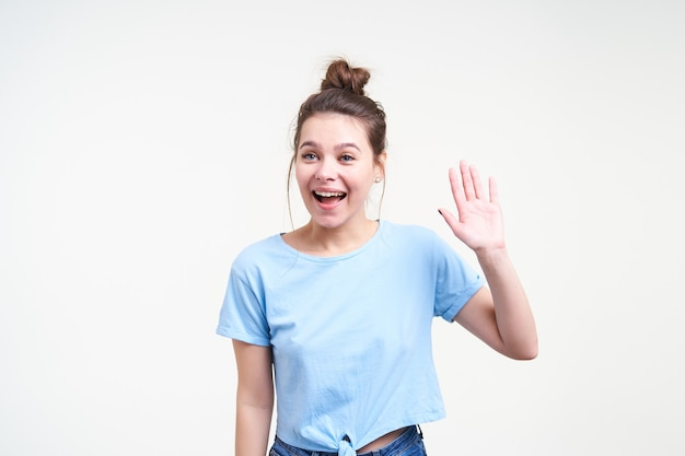 Enthousiaste jeune belle femme aux cheveux noirs aux yeux bleus avec une coiffure décontractée, levant la main en bonjour geste tout en regardant joyeusement de côté, debout sur fond blanc