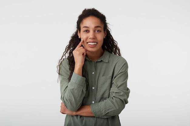 Enthousiaste jeune belle femme frisée aux cheveux noirs avec une peau foncée gardant la main levée sur sa joue et souriant joyeusement à la caméra, posant sur fond blanc