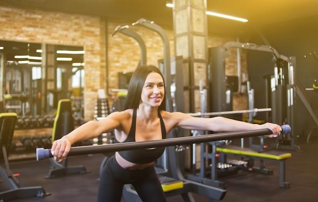 Enthousiaste jeune brune en tenue de sport faisant des exercices de gymnastique avec barre de corps dans sa main dans la salle de sport