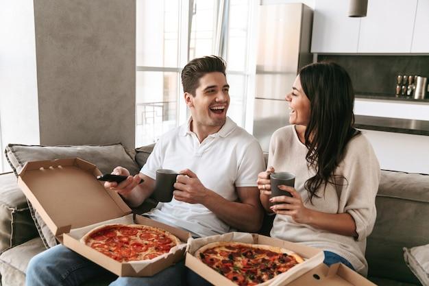 Enthousiaste jeune couple assis sur un canapé à la maison, manger de la pizza