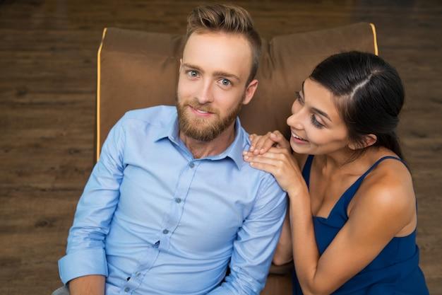 Enthousiaste jeune couple assis sur le canapé et souriant