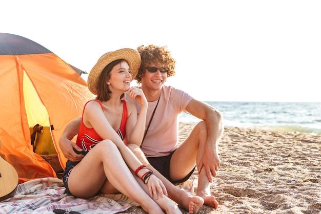 Enthousiaste jeune couple assis ensemble à la plage, camping