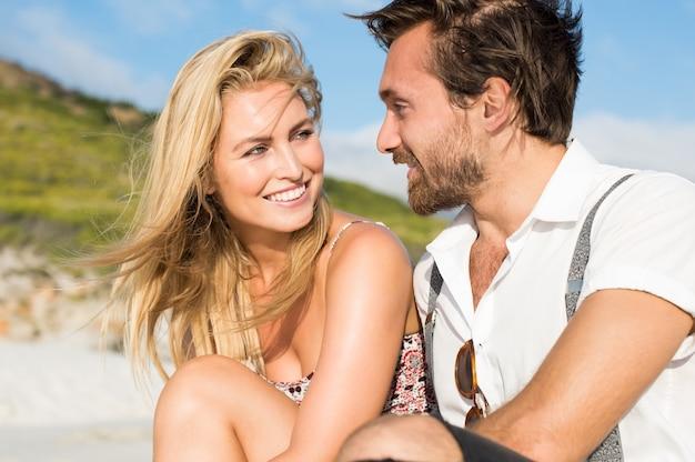 Enthousiaste jeune couple assis sur la plage en se regardant