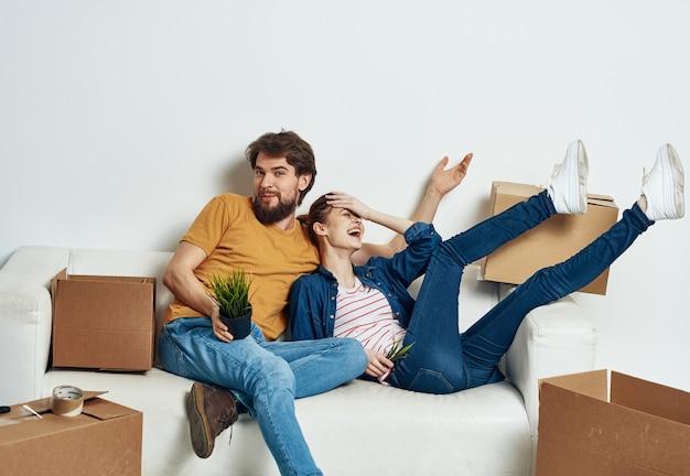 Enthousiaste jeune couple dans la chambre sur le canapé avec des boîtes
