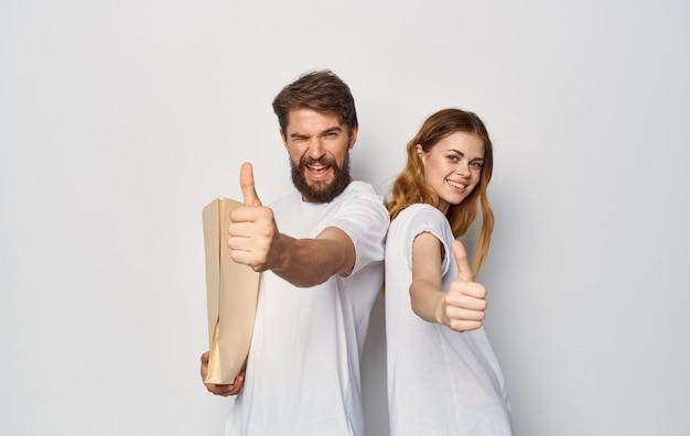 Enthousiaste jeune couple dans un paquet de t-shirts blancs avec des produits d'épicerie en cours d'exécution.