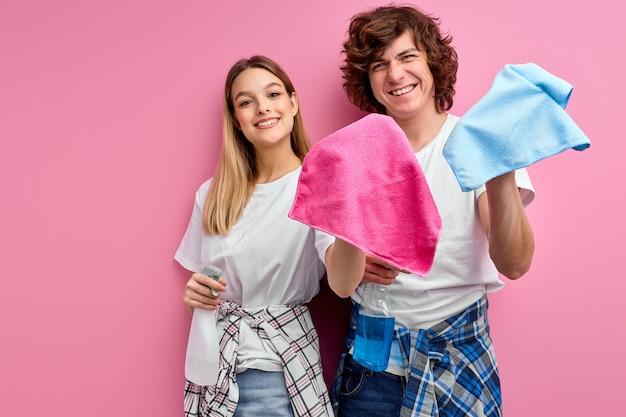 Enthousiaste jeune couple de famille caucasien ont des expressions faciales positives, utilisez des chiffons et vaporisez