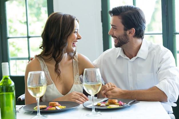 Enthousiaste jeune couple main dans la main à la table du restaurant