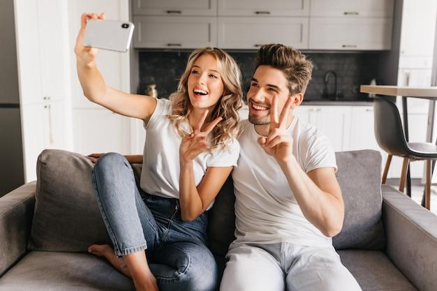 Enthousiaste jeune couple à la maison faisant selfie avec signe de paix et souriant largement. fille heureuse assise sur le canapé avec son petit ami et en prenant le portrait d'eux ensemble.
