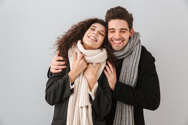 Enthousiaste jeune couple portant des chandails et des écharpes debout isolé sur mur gris, hugigng