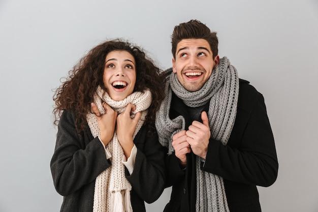 Enthousiaste jeune couple portant des chandails et des écharpes debout isolé sur mur gris, levant les yeux
