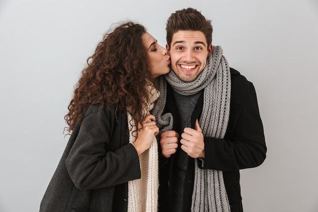 Enthousiaste jeune couple portant des chandails et des écharpes debout isolé sur un mur gris, s'embrasser
