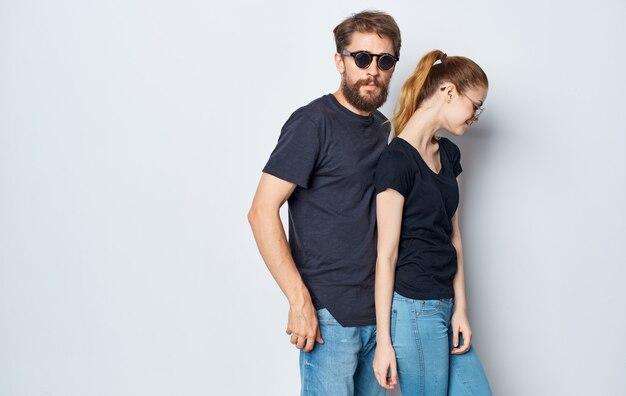 Enthousiaste jeune couple portant des lunettes de soleil tenue décontractée studio communication fond isolé