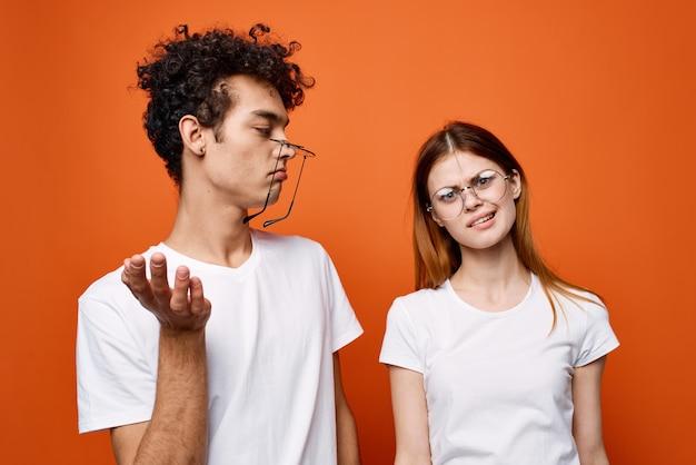 Enthousiaste jeune couple en t-shirts blancs portant des lunettes