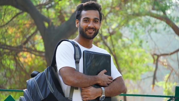 Enthousiaste jeune étudiant avec ordinateur portable à la recherche
