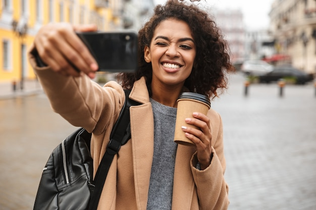Enthousiaste jeune femme africaine portant manteau marchant à l'extérieur, tenant une tasse de café à emporter, prenant un selfie