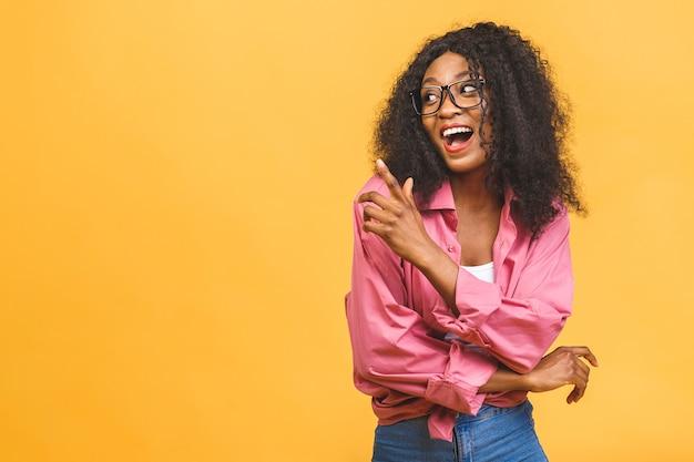 Enthousiaste jeune femme afro-américaine aux cheveux bouclés avec un sourire heureux.