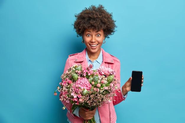 Enthousiaste jeune femme afro-américaine tient le bouquet de fleurs montre smartphone avec affichage maquette sourit positivement bénéficie de vacances spéciales