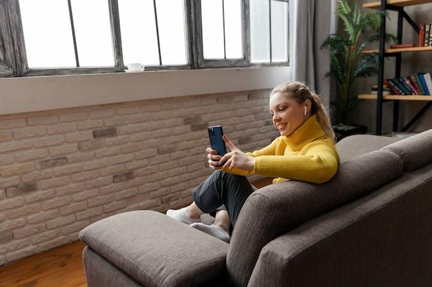 Enthousiaste jeune femme à l'aide de téléphone portable assis sur un canapé à la maison. photo de haute qualité