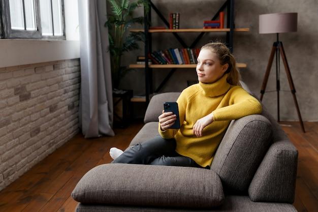 Enthousiaste jeune femme à l'aide de téléphone portable assis sur un canapé à la maison.