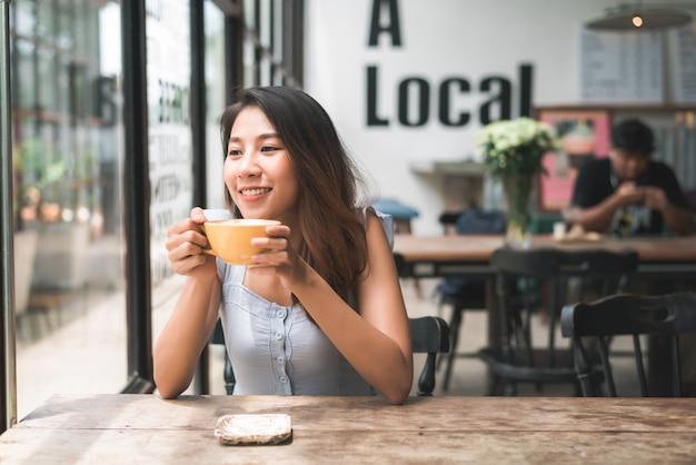 Enthousiaste jeune femme asiatique buvant du café chaud ou du thé en profitant de assis dans un café
